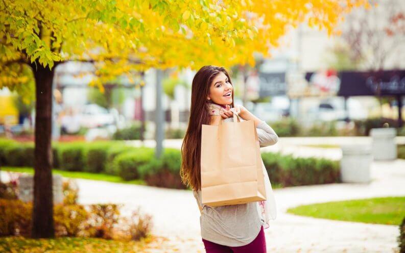 young women walking down a street carrying shopping bags