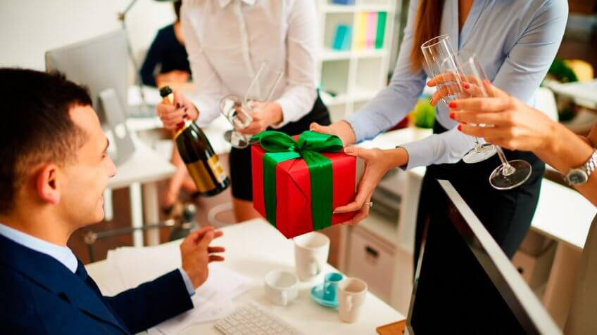 Businesswoman giving gift box to colleague