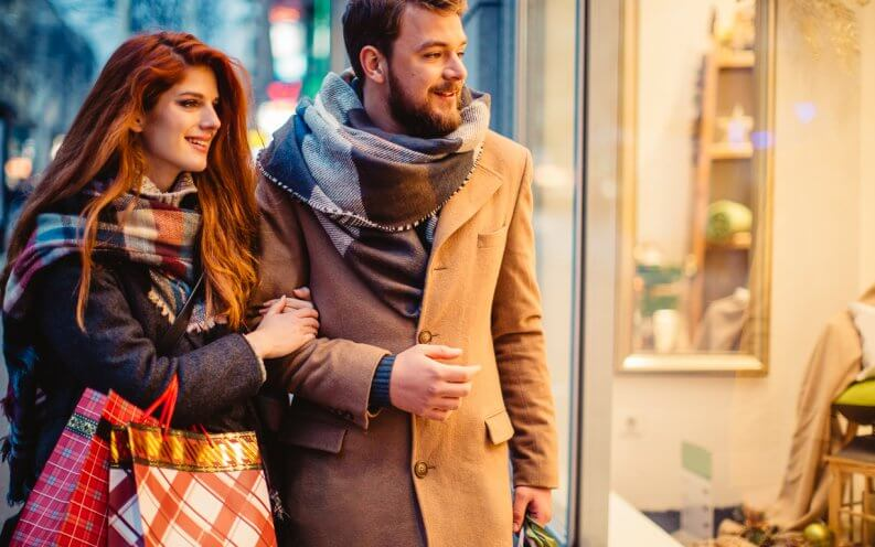 Couple window shopping outdoors in winter city street.