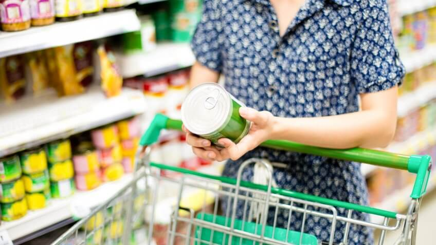 woman looking at canned good
