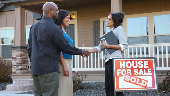 Couple shakes hands with realator in fron of new home.