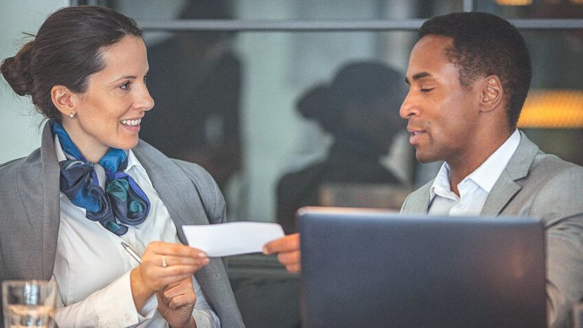 Young businesswoman and man working together on a laptop, and having a business conversation in a modern office space.