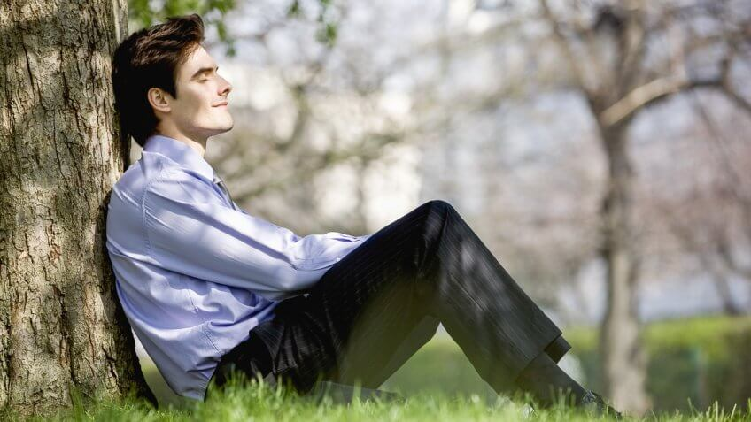 content man sitting against a tree in the park