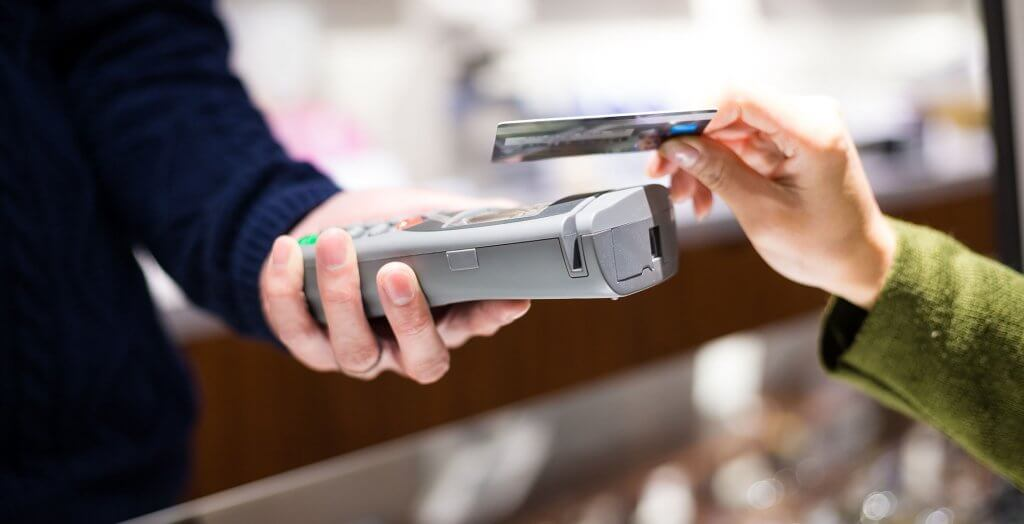 woman handing credit card to cashier holding card reader