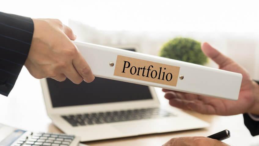 man handing portfolio binder to another man