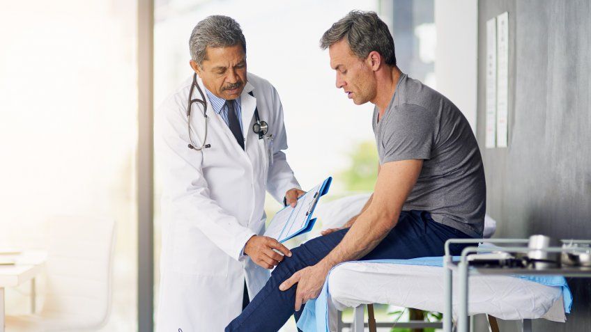 Shot of a mature doctor examining his patient who is concerned about his knee.