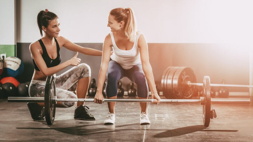 10 Best and Worst Industries for Work-Life Balance, Young woman exercising at the gym with a female personal trainer