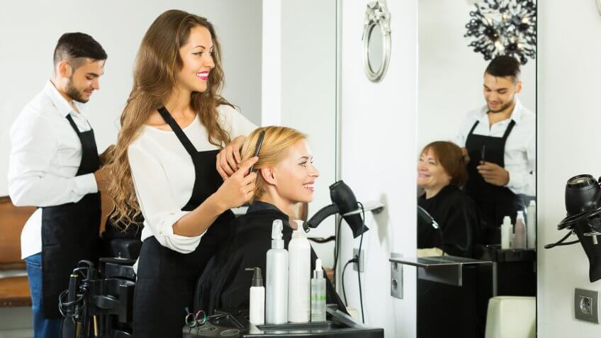 10 Best and Worst Industries for Work-Life Balance, Happy woman hairdresser doing hairstyle for young men