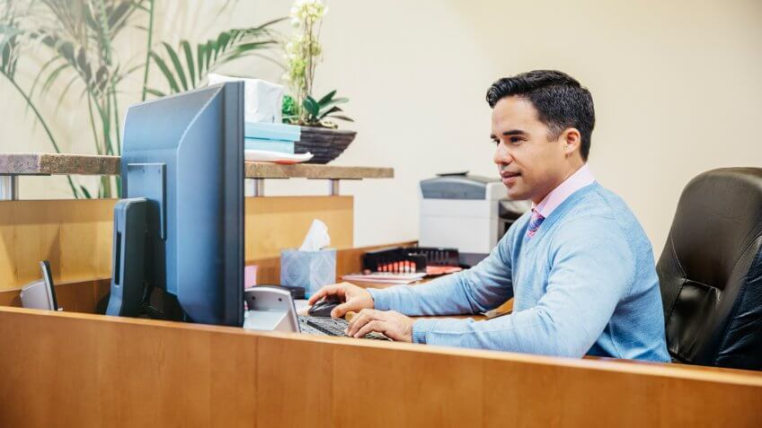 10 Best and Worst Industries for Work-Life Balance, 40-44 years, Business, Businessman, Caucasian, Computer, Cubicle, Desk, E-Mail, Head And Shoulders, Internet, Latin American and Hispanic Ethnicity, Mature Men, Office, One Person, San Diego, Secretary, Sweater, Technology, Working, access, brunette, business attire, california, color image, concentrating, connection, e-mailing, focusing, horizontal, indoors, lobby, man, mature adult, mixed race person, office life, online, people, photography, reading, side view, sitting, united states, viewing