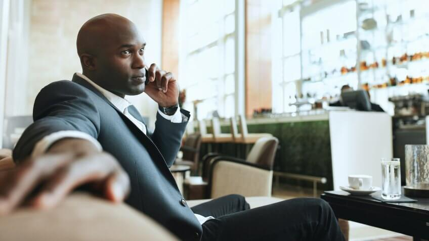 10 Best and Worst Industries for Work-Life Balance, African business man talking on mobile phone while waiting in a