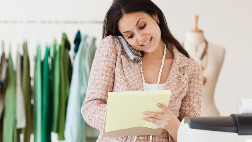 10 Best and Worst Industries for Work-Life Balance, 20-24 years, Boutique, Cashier, Clothing, Clothing Store, Concentration, Fashion, Hanging, Head And Shoulders, Latin American and Hispanic Ethnicity, Listening, One Person, One Young Woman Only, Owner, Retail, Small Business, Store, Telephone, Working, Writing, Young Adult, answering, calling, career, cash register, clerk, clothing shop, color image, cordless telephone, customer service, enjoying, front view, getting things done, happy, horizontal, independent, indoors, jersey city, landline, latina, legal pad, looking down, mixed race person, multi-tasking, new jersey, ordering, people, phoning, photography, propping, sitting, smiling, talking, wireless technology, woman