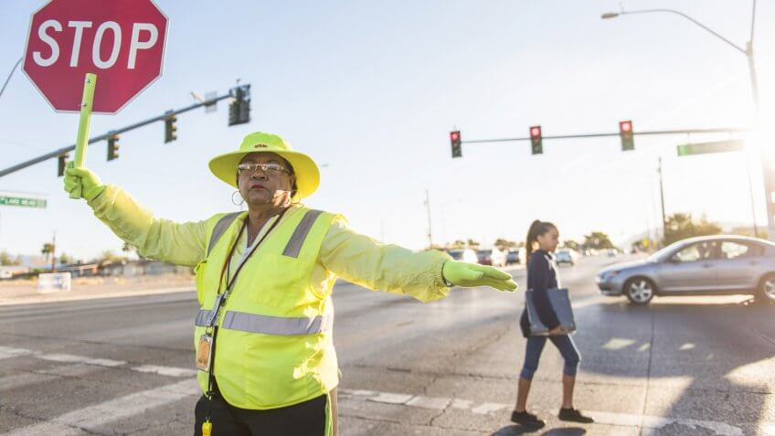 Crossing guard Patricia Bass assists a child in crossing Lake Mead Boulevard at Tonopah Drive before classes at West Preparatory Academy in Las Vegas, Thursday, Oct.