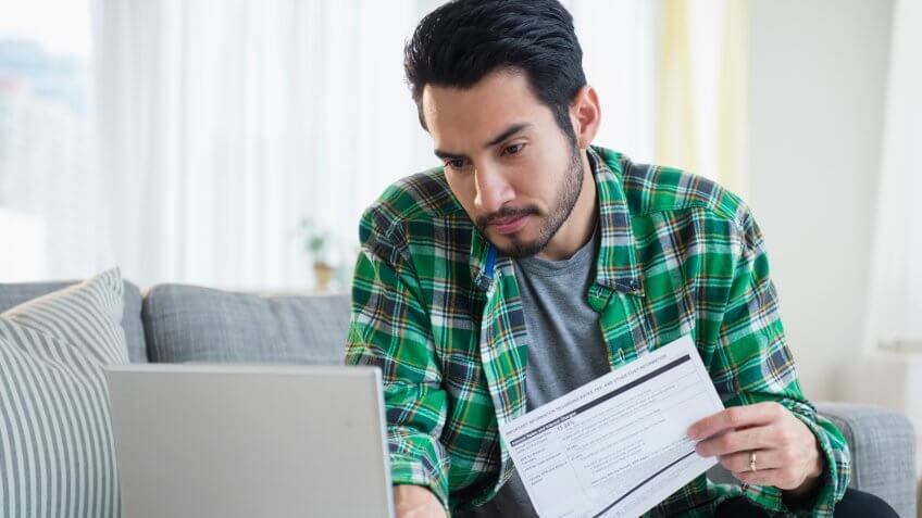 Mixed race man paying bills in living room.