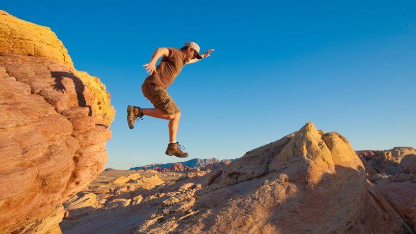 A man leaps down from a mountain.