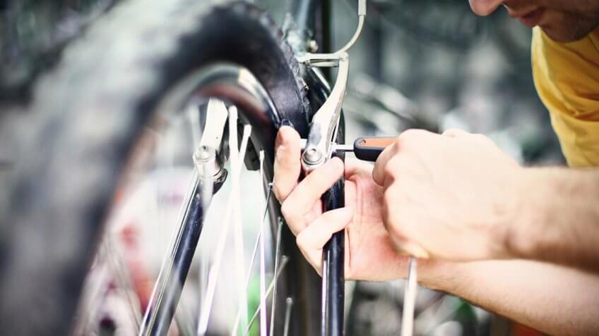 person fixing bike brakes