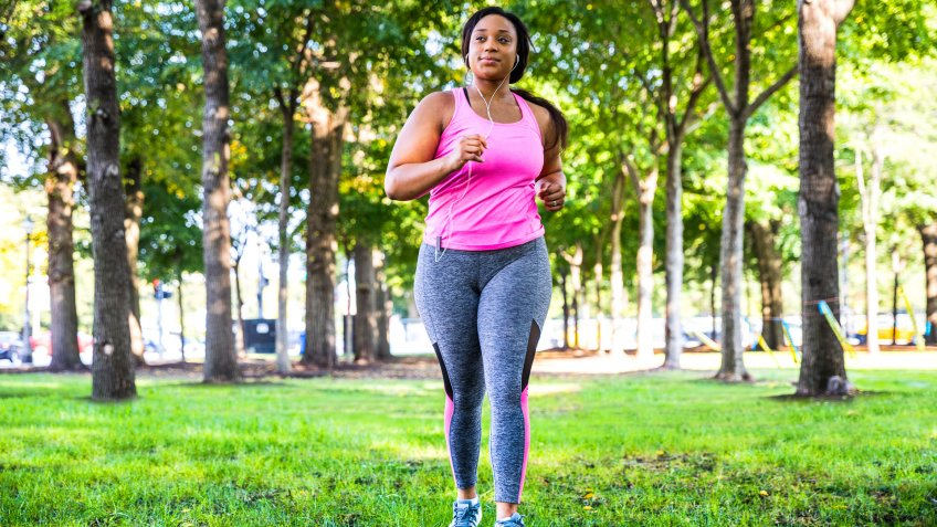 Plus size women jogging and exercising at the park and walking outdoor in the city streets in Chicago, United States - USA.