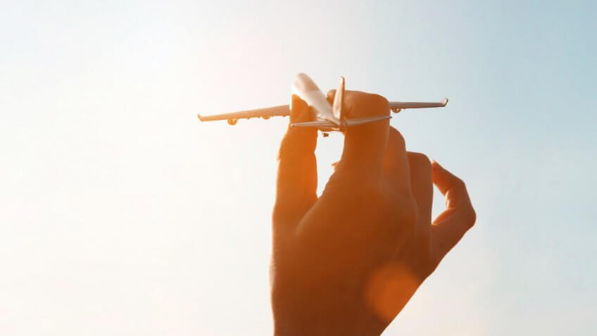 hand playing with miniature airplane
