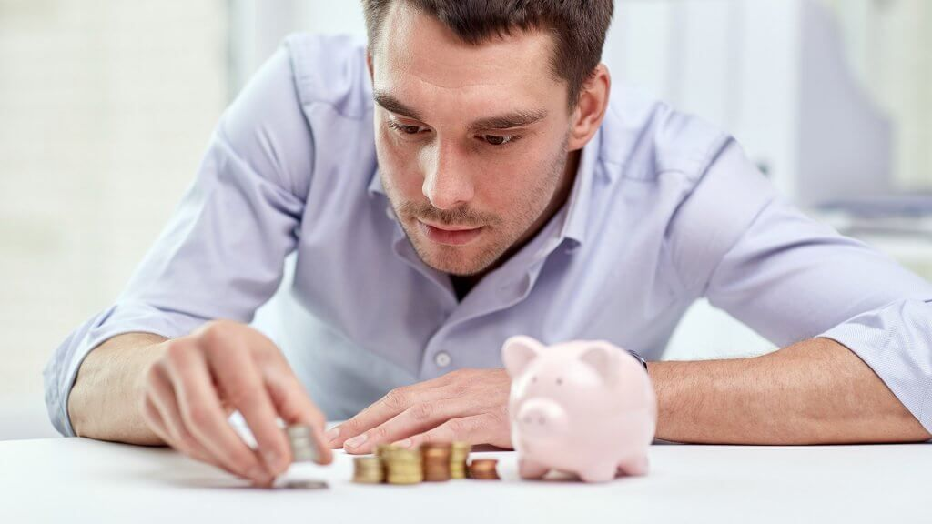 man carefully placing coins in stacks next to piggy bank
