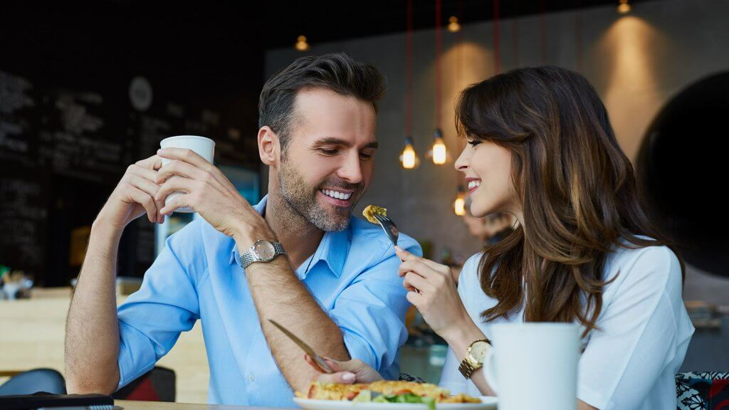 woman using fork to feed piece of food to boyfriend