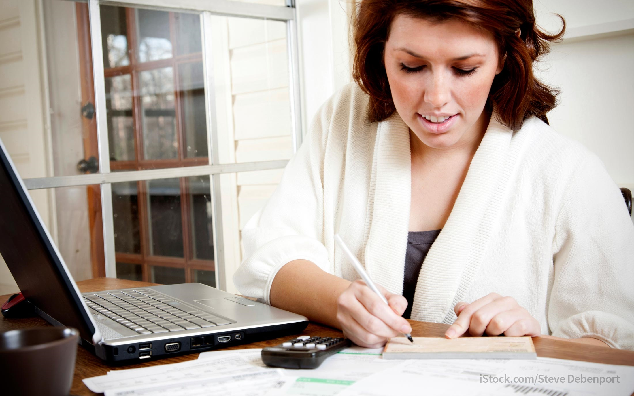 women writing check to save money on taxes