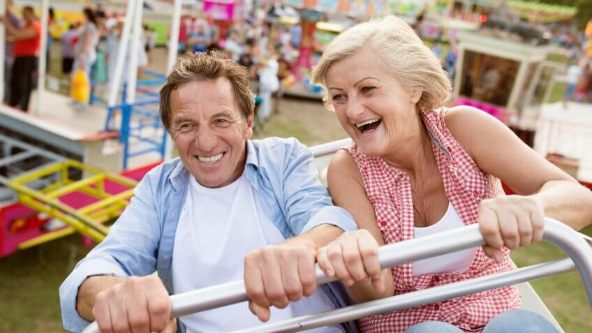 Senior couple having fun on a ride in amusement park.
