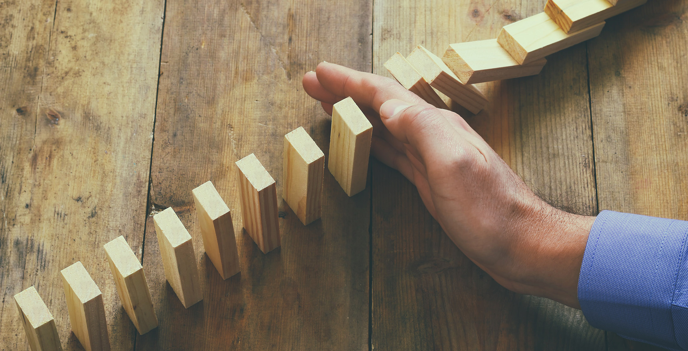 hand blocking row of wooden blocks from falling