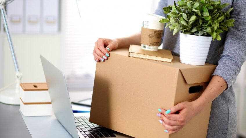 close up of woman holding storage box and laptop
