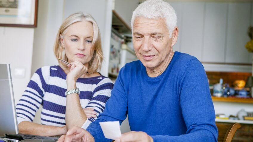 older couple studying piece of paper near laptop