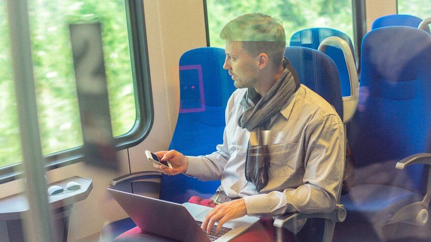 young man using his computer and smartphone on a train