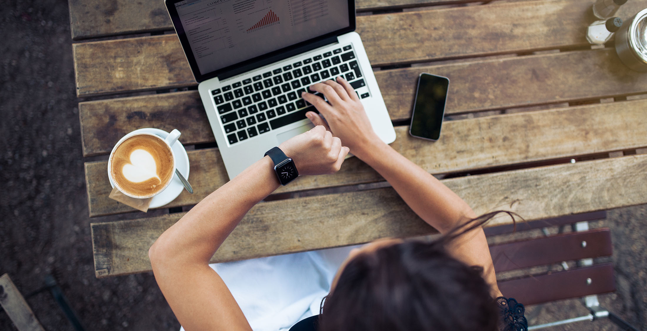 overhead shot of woman checking watch at computer drinking latte