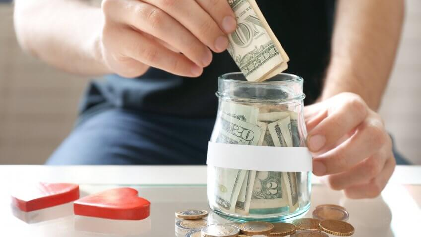 close up of man placing dollar bills in a jar