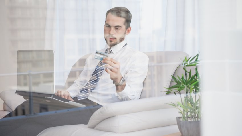 Businessman shopping online on his couch seen through glass at home in the living room.