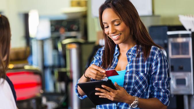 Coffee shop cashier swiping card on digital tablet reader.