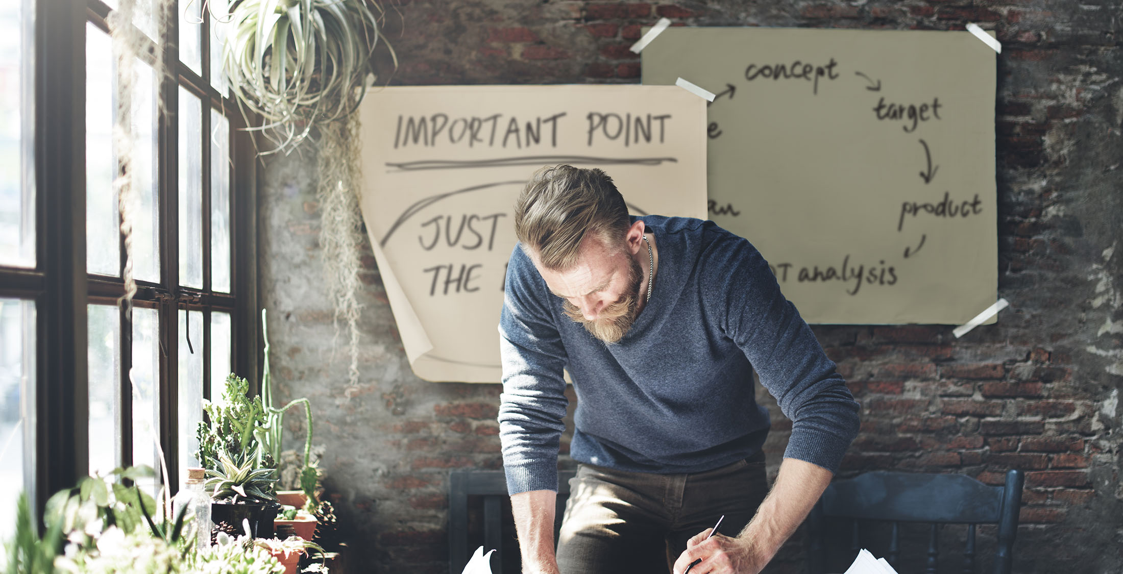 man writing at desk near window with plants