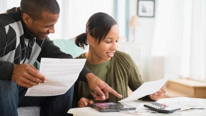 Couple paying bills in living room.