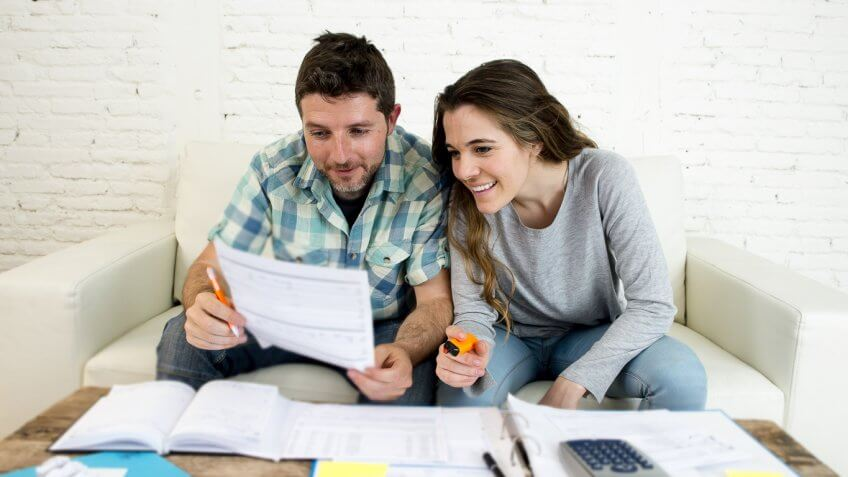 happy young couple reviewing documents on couch