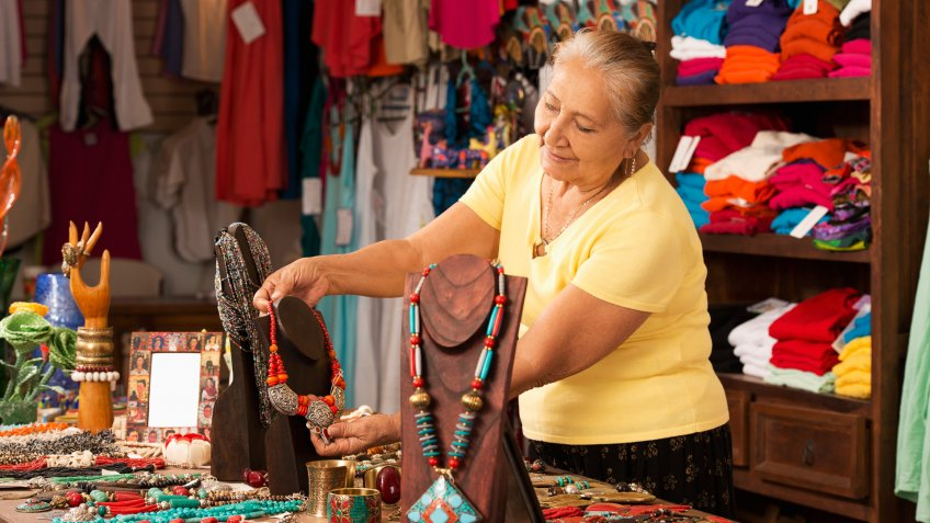 Smiling woman working in traditional gift shop.