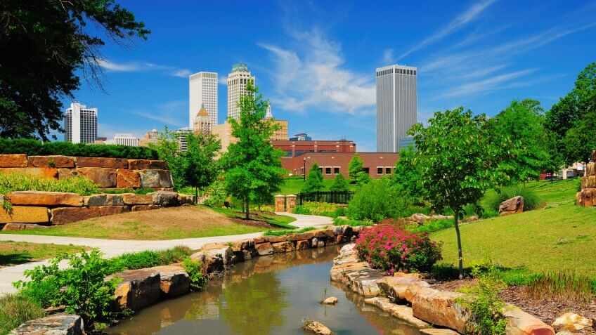 Tulsa downtown skyline from a park with trees, grass, rocks, and a stream in the foreground.