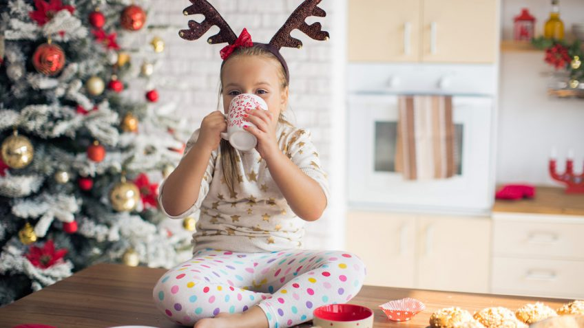 young girl drinking from a mug at Christmas