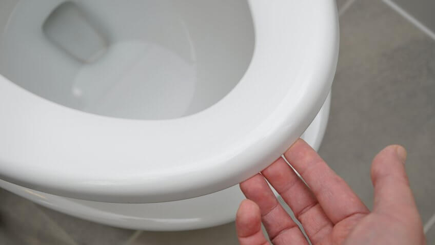 person lifting up toilet seat