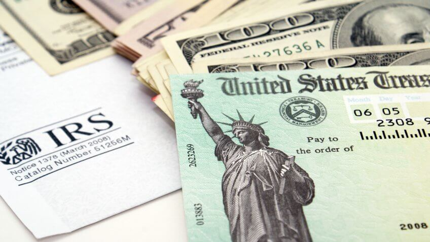 Stimulus economic tax return check and USA currency.