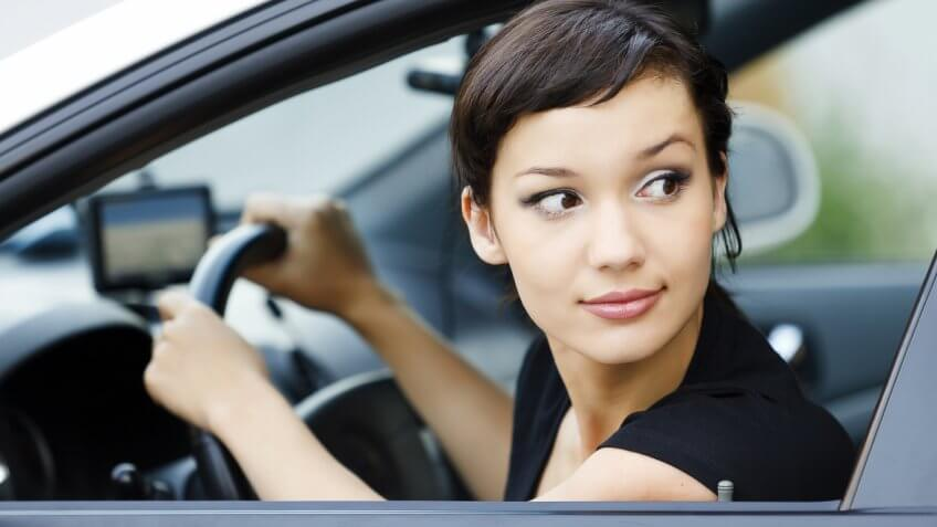 woman looking outside of the window while driving