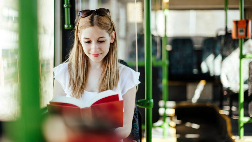 young woman reading on a public bus