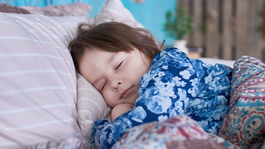small child sleeping on a bed