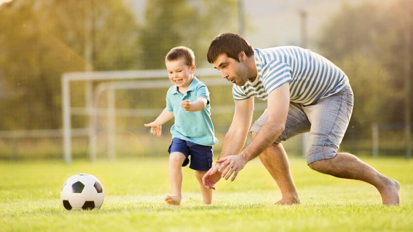 father and toddler playing on soccer field