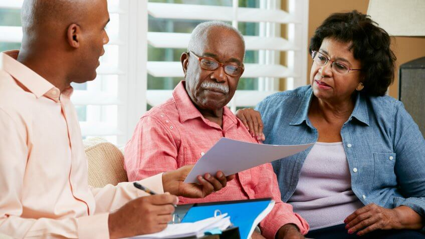 Financial Advisor Talking To Senior Couple At Home Showing Documents.