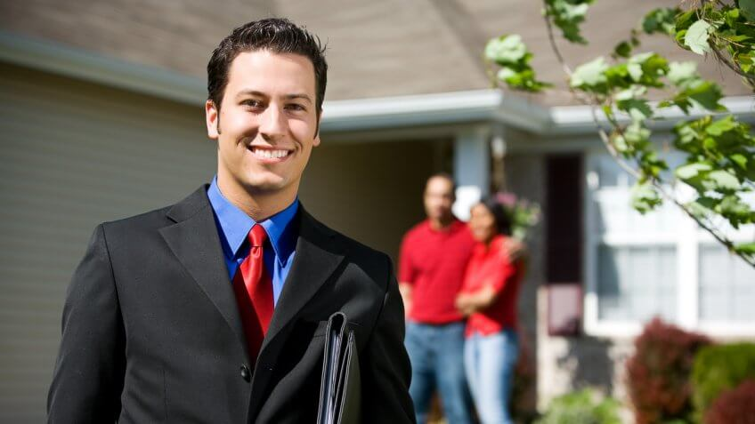 realtor posing for a picture with homeowners in the background