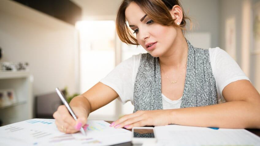 young woman filling out paperwork at home