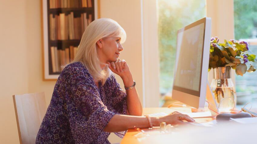 Senior woman working at computer in home office