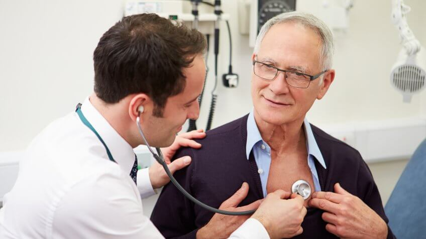 Doctor Examining Senior Male Patient In Hospital Listening To Heartbeat Using Stethoscope.